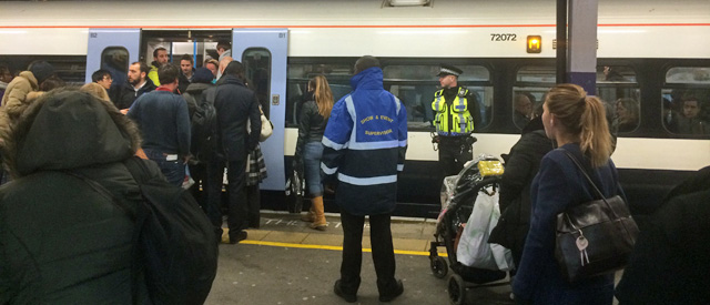On guard: Police and security officers watch Lewisham station at the end of last Tuesday's rush hour