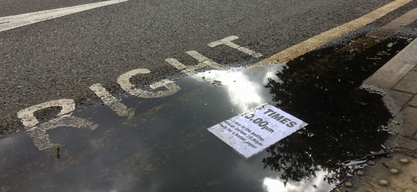 Polling station sign in a puddle in Westcombe Park Road